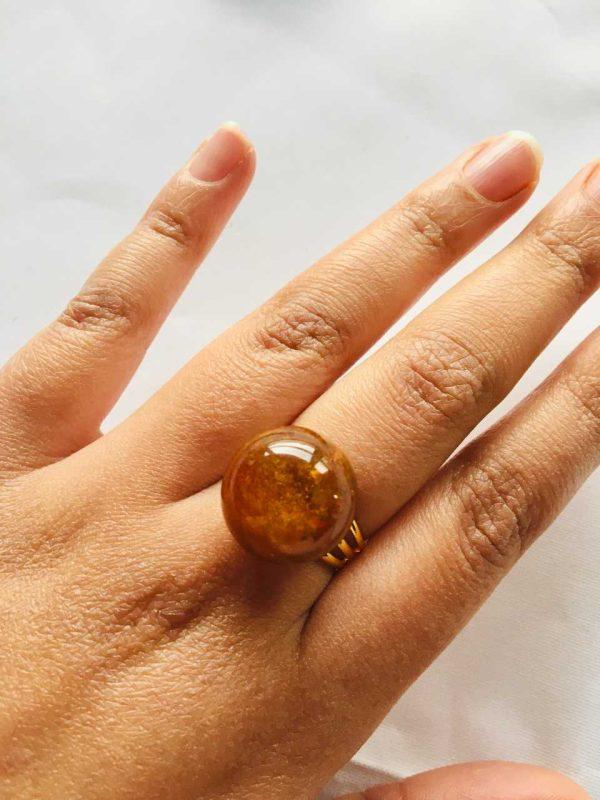 Bague en résine créée par adaval Bijoux. Ici la bague est montée avec une sphère marron avec des inclusions de poudre de nacre. Bijou unique .