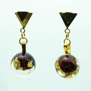 Boucles d'oreilles agrémentées d'une sphère en résine. Ici elles sont incrustées de baie rouge et de feuilles d'or.