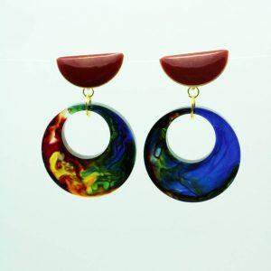 Boucles d'oreilles en résine par Adaval Bijoux. Elles sont rondes, avec un effet marbré multicolore de rouge, bleu, jaune. Fait à la main dans les hauts de France.