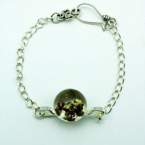 Bracelet fleur en résine avec une inclusion de vraies fleurs séchées violettes. Fabrication artisanale par Adaval Bijoux.