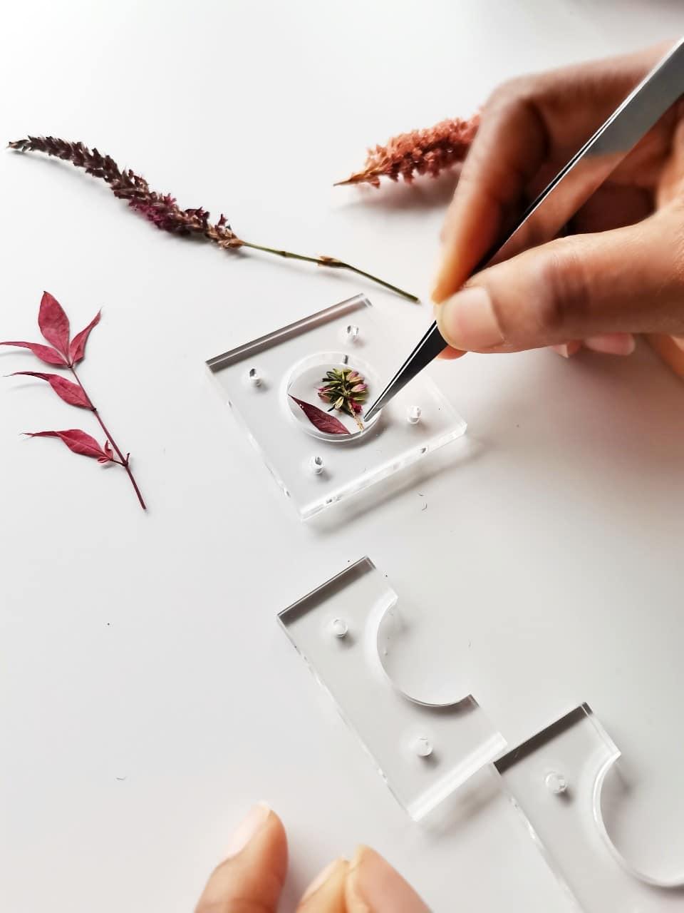 Photo montrant l'incrustation de fleurs lors de la réalisation  des bijoux résine par adama valentini